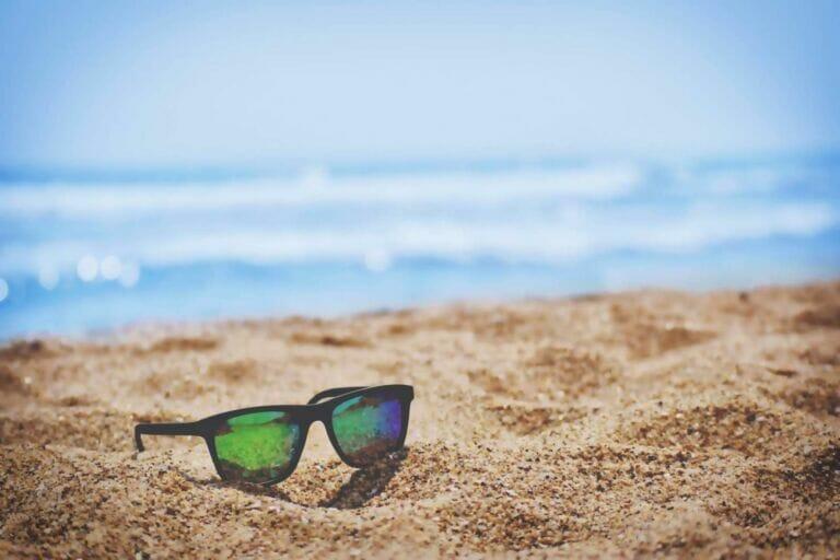 Sonnenbrille liegt auf Sand am Meer