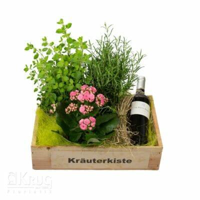 Holzkiste mit Kräuter-Pflanzen und einer Wein Flasche